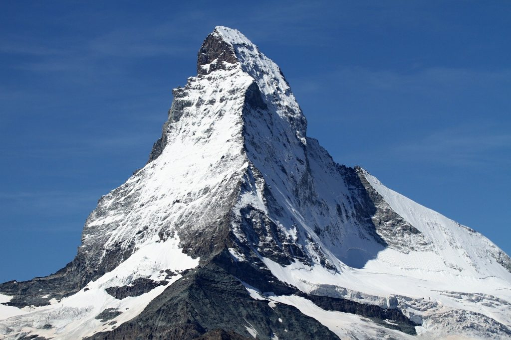 A snow-covered mountain peak, spelled P-E-A-K, against a bright blue sky