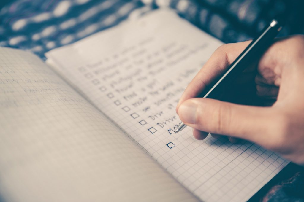 notebook with a list being written. A hand holding a pen is adding to it.